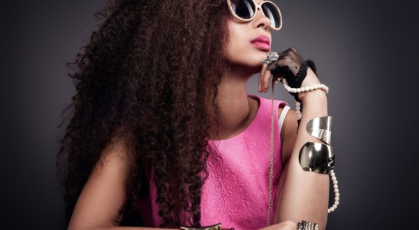 43008986 - fashion photo of beautiful elegant african american woman. girl posing with a lot of jewelry, wearing fashionable sunglasses. girl with long curly healthy hair. beauty portrait. studio shot.